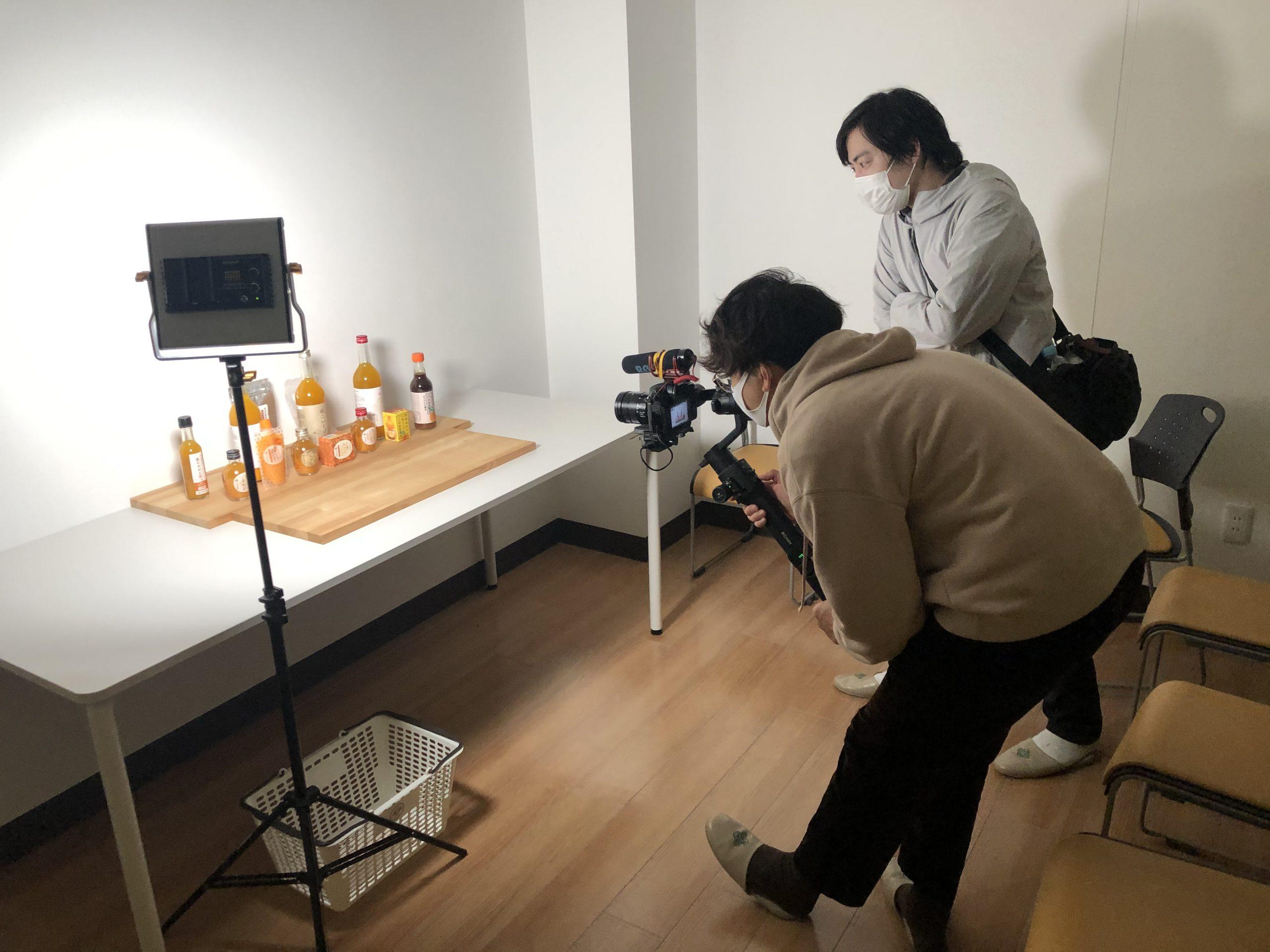 ディレクターの清水さんと、フォトグラファーの山本さんが、ジュースなどの加工品を並べて動画撮影を行っている風景。