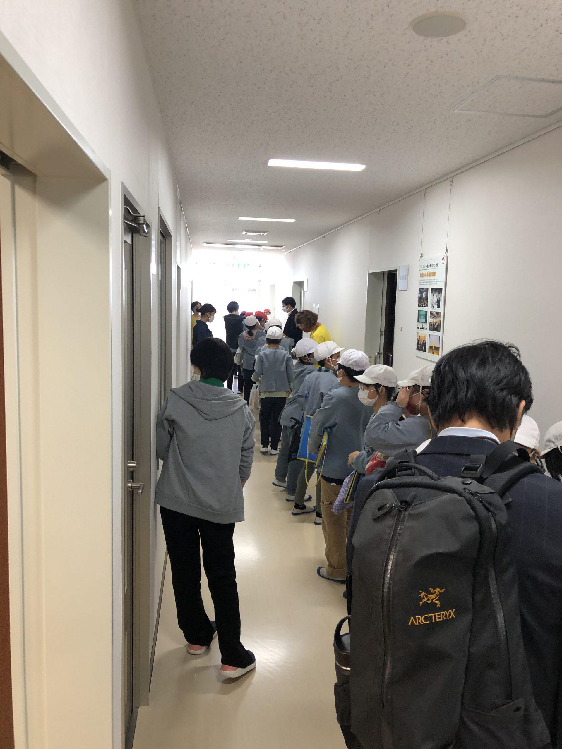3階大会議室へ続く廊下に、一列に並んで入室する様子。