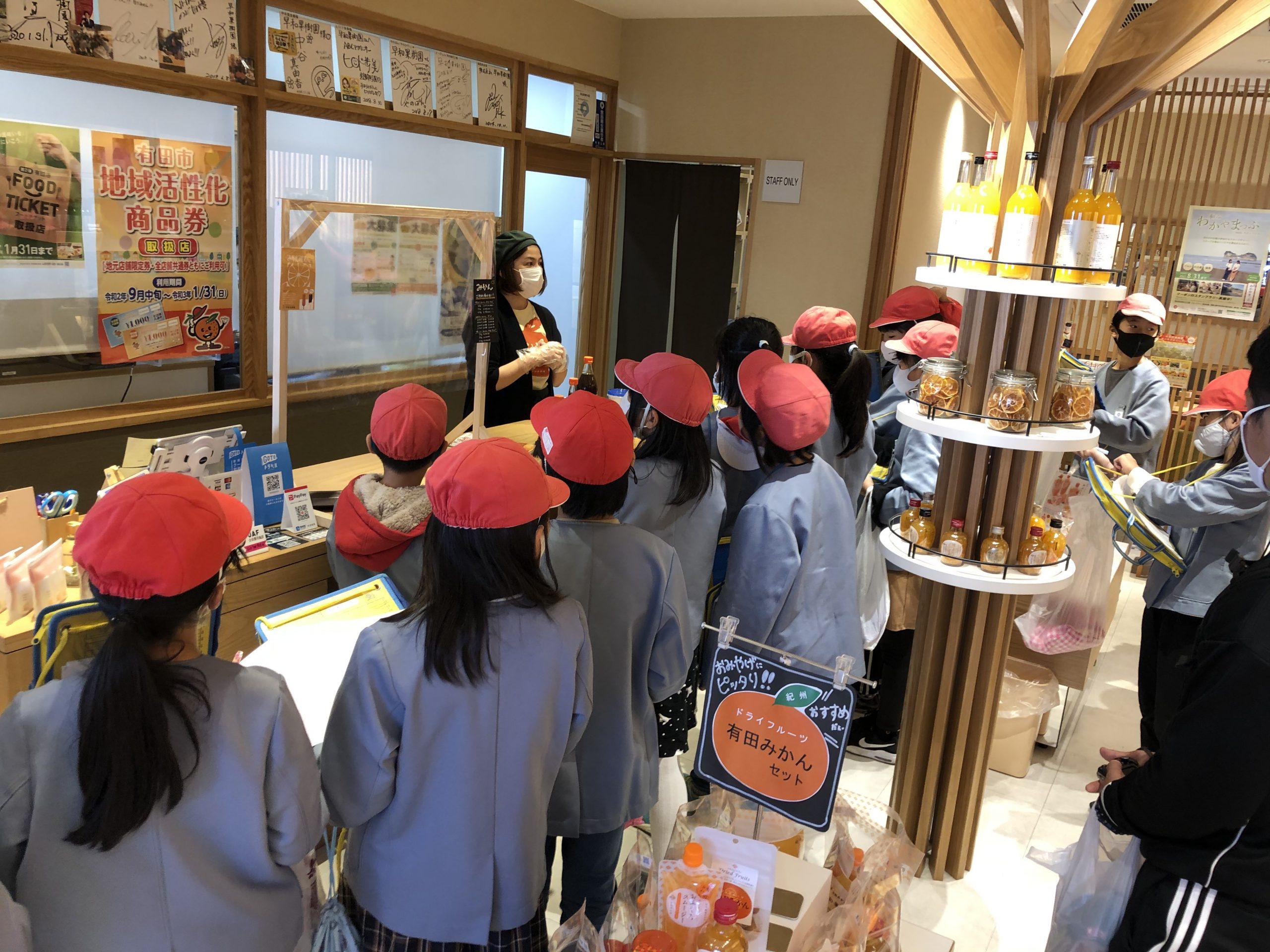 ショップ内で、スタッフに商品についての質問をする生徒さんたち。