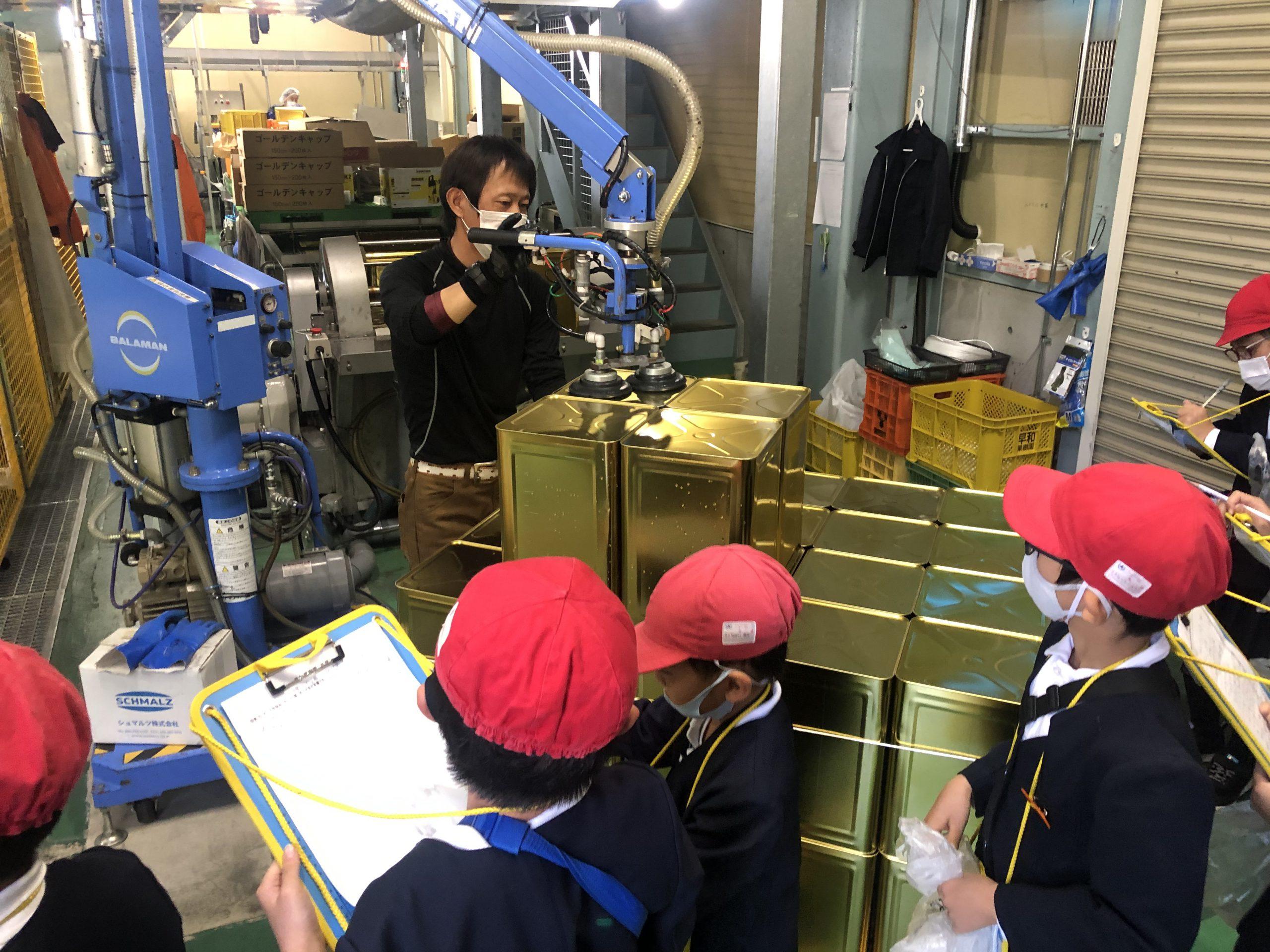 一斗缶に充填されたジュースを機械を使って移動、積み上げの様子を見学。
